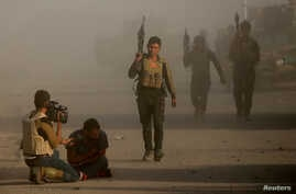 An Iraqi journalist reacts after an Islamic State suicide bomber attacked an Iraqi special forces unit with a car bomb during clashes in Bartella, east of Mosul, Iraq, Oct. 20, 2016.