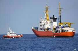 "An Italian Coast Guard boat, left, approaches the French NGO ""SOS Mediterranee"" Aquarius ship, in the Mediterranean Sea, June 12, 2018. Italy dispatched two ships Tuesday to help take 629 migrants stuck off its shores on the days-long voyage to Spain"