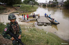 FILE - A soldier stands guard on the Thai side of the river as people prepare to cross into Malaysia in Sungai Kolok in southern Narathiwat province, March 8, 2013.