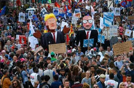 Protesters carry effigies of US President Donald Trump and Belgian PM Charles Michel during a demonstration in the center of Brussels, May 24, 2017. Demonstrators marched in Brussels ahead of a visit of US President Donald Trump and a NATO heads of s...