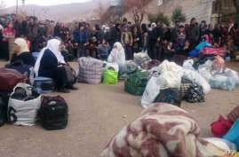 Syrians wait for the arrival of an aid convoy on Jan. 11, 2016 in the besieged town of Madaya as part of a landmark six-month deal reached in September for an end to hostilities in those areas in exchange for humanitarian assistance.