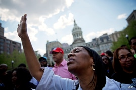 Patricia Freeman prays during a rally in front of City Hall, Sunday, May 3, 2015, in Baltimore.
