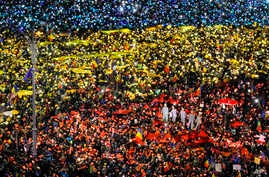 People light the flashes of their mobile phones in the colors of Romania's flag during an anti-government protest in Bucharest, Romania, Feb. 12, 2017.