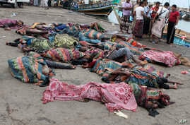 FILE - Bodies of Somali migrants, killed in attack by a helicopter while traveling in a boat off the coast of Yemen, lie on the ground at Hodeida city, Yemen, Mar. 17, 2017.