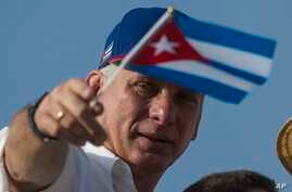 FILE - Cuba's President Miguel Diaz-Canel holds a national flag while watching the May Day parade file past at Revolution Square, in Havana, Cuba, May 1, 2018.