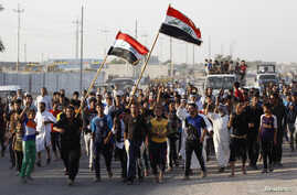 Volunteers, who have joined the Iraqi army to fight against militants from the radical Islamic State of Iraq and the Levant (ISIL), carry weapons and wave Iraqi flags during a parade in the streets of eastern Baghdad June 15, 2014.
