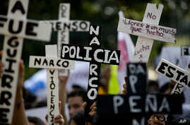 "Demonstrators march with crosses with writing that reads in Spanish ""Narco Cops"" in protest for the disappearance of 43 students in the state of Guerrero, in Mexico City, Nov. 5, 2014."