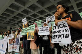 FILE - A migrant workers alliance group holds placards to protest the killings of two Indonesian women in 2014 outside the High Court in Hong Kong, Oct. 24, 2016.