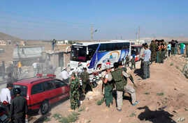 This photo released by the Syrian official news agency SANA, shows Syrian troops, journalists and civilians watching as buses evacuate people from the two pro-government villages of Foua and Kfarya, at Tel el-Eis, the crossing between Aleppo and Idli