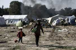 Migrants carry their belongings as they leave from a makeshift camp during a police operation at the Greek-Macedonian border near the northern Greek village of Idomeni, May 26, 2016.