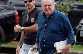 A federal police officer escorts Brazil's former Agriculture Minister Wagner Rossi into Federal Police headquarters in Sao Paulo, Brazil, March 29, 2018.