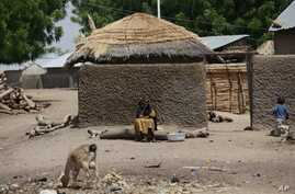 FILE - A woman sits outside her home in Chibok, Nigeria, May 19, 2014. Boko Haram fighters are overrunning villages near the northeastern Nigerian town, forcing hundreds of people to flee as the insurgents loot and burn in the area where nearly 300 s