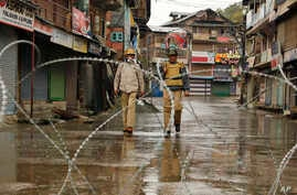 Barbed wires are set up as road blockade as Indian policemen patrol during a strike in Srinagar, Indian controlled Kashmir, Oct. 19, 2015.
