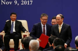 FILE - Vice chairman and president of China Investment Corporations (CIC) Tu Guangshao, chairman of the Board of Directors of the Bank of China Chen Siqing and president of Sinopec Group Dai Houliang attend signing ceremony and meeting of business le