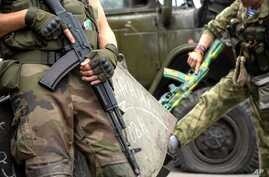 Pro-Russian rebels hold their guns as they patrol the Lenin square in the town of Donetsk, eastern Ukraine, Aug. 28, 2014.
