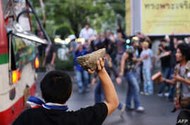 Thai opposition protesters attack a bus carrying pro-government Red Shirt supporters on their way to a rally at a stadium in Bangkok, Nov. 30, 201