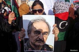 A woman holds a portrait of former Libyan army officer Khalifa Haftar, during a rally supporting Haftar, in Benghazi, Libya, Aug. 1, 2014.