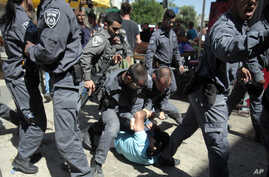 Israeli police officers detain a Palestinian man as Israeli youths enter Jerusalem's Old City through Damascus Gate during a march celebrating Jerusalem Day, Sunday, May 17, 2015.