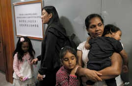 FILE - Asylum seekers Nadeeka Dilrukshi Nonis, right, with her son Dinath and daughter Sethmundi Kellapatha and Vanessa Mae Rodel with her daughter Keana wait at the office of Torture Claims Appeal Board in Hong Kong Monday, July 17, 2017.