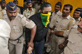 An accused man (face covered), surrounded by Indian policemen, is taken to a court in Mumbai, India, Sept. 11, 2015.