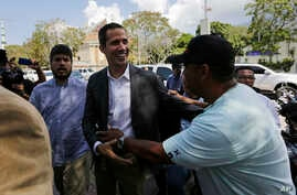 Venezuelan Congress President Juan Guaido, an opposition leader who has declared himself interim president, greets a supporter as he arrives to meet with public employee unions in Caracas, March 5, 2019.