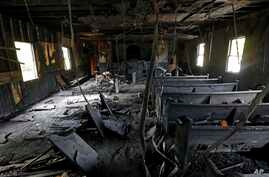 Burned pews, destroyed musical instruments, Bibles and hymnals are part of the debris inside the fire damaged Hopewell M.B. Baptist Church in Greenville, Mississippi, Nov. 2, 2016.