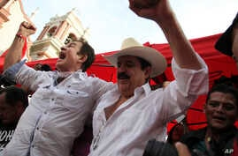 Opposition leader Salvador Nasralla, left, cheers along with former President Manuel Zelaya, at a rally where he reaffirmed his claim on the presidency of Honduras, in the central park of San Pedro Sula, Honduras, Jan. 6, 2018.