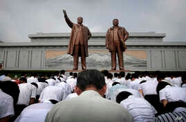 North Koreans bow in front of bronze statues of the late leaders Kim Il Sung, left, and Kim Jong Il at Munsu Hill in Pyongyang, North Korea, July 27, 2015. These two bronze statues were created by artists from Mansudae Art Studio.