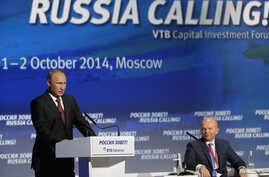 "Russia's President Vladimir Putin (L) speaks during the VTB Capital ""Russia Calling!"" Investment Forum in Moscow October 2, 2014."
