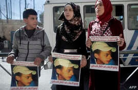 Relatives of Palestinian teenager Mohammed Abu Khdeir who was killed in 2014, hold posters bearing his portrait outside the Jerusalem district court during a hearing on Feb. 4, 2016.