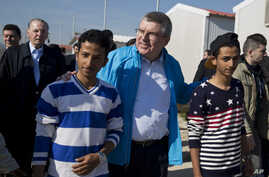 IOC President Thomas Bach, center, walks with two young refugees with former IOC President Jacques Rogge in the background, during their visit at a refugee camp in Athens, Greece, Jan, 28, 2016.