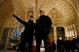 French Police officers stand near the entrance of Notre Dame Cathedral as worshippers arrive for the Christmas eve mass in Paris, France, Dec. 24, 2016. Security was tightened at Christmas across Europe after a deadly truck attack on a market in Berl