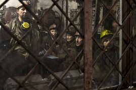 Ukrainian coal miners wait in a room before going underground at the Zasyadko mine in Donetsk, Ukraine, Wednesday, March 4, 2015. An explosion ripped through a coal mine before dawn Wednesday in war-torn eastern Ukraine, killing at least one miner an