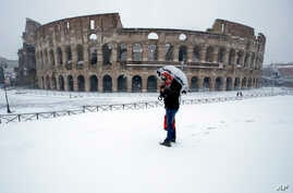 A man stands in front of the ancient Colosseum blanketed by the snow in Rome, Feb. 26, 2018.