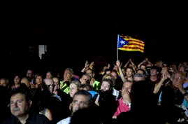 A man waves an Estelada or Independence flag during an event promoting the start of campaigning for a referendum on Catalonia's future status, in Tarragona, Spain, Sept. 14, 2017.