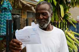"William Jones, upset with the unresponsiveness of his electric company, displays his monthly bill. ""Answer the phone when you call them,"" he complains. ""Answer the phone."" (Photo: R. Taylor / VOA)"