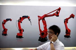 FILE - In this Aug. 15, 2018, file photo, a visitor talks on his smartphone in front of a display of manufacturing robots from Chinese robot maker Honyen at the World Robot Conference in Beijing, China. China will make economic changes at its own pac