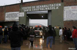 Relatives of inmates wait for news at the entrance of Palmasola Penitentiary Complex in the outskirts of Santa Cruz, Bolivia, Aug. 23, 2013.