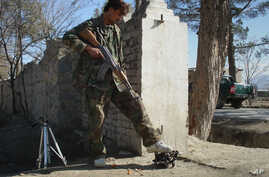 FILE - An Afghan security officer steps on a wreckage of a suicide attacker's car near U.S. Forward Operating Base Chapman in Khost province, Afghanistan, Jan. 19, 2009.