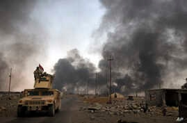 FILE - Iraqi security forces patrol as smoke rises from burning oil wells in Qayara, south of Mosul, Iraq, Aug. 31, 2016. As Iraqi and coalition forces prepare to move on Mosul, IS fighters reportedly are digging trenches around the city which they p...