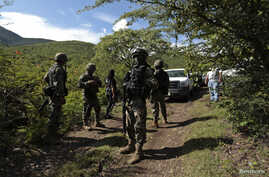 Soldiers guard an area where a mass grave was found, in Colonia las Parotas on the outskirts of Iguala, in Guerrero, Mexico, Oct. 4, 2014.