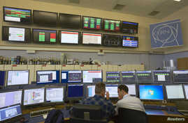 FILE - Technicians work in the Control Centre of the Large Hadron Collider (LHC) at the European Organisation for Nuclear Research (CERN) in Prevessin near Geneva, March 11, 2015.
