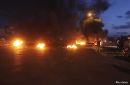 Burning obstacles are seen along a road leading to the airport in Tripoli, Libya, April 7, 2014.