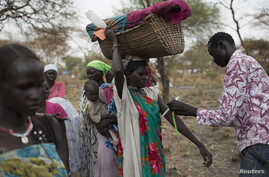 A mother carrying her baby in a basket is screened for malnutrition at a joint UNICEF-World Food Program Rapid Response Mission, which delivers critical supplies and services to those displaced by conflict, in Nyanapol, South Sudan, March 3, 2015.