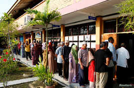 People line up to vote during the general election in Alor Setar, Malaysia, May 9, 2018. By 1 p.m. about 55 percent of the eligible voters had cast ballots.