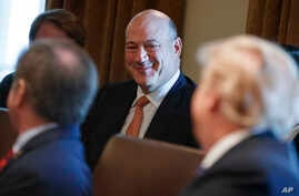 President Donald Trump speaks to outgoing White House chief economic adviser Gary Cohn during a cabinet meeting at the White House, March 8, 2018, in Washington.