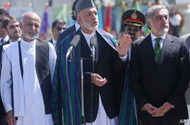 Afghan President Hamid Karzai, center, speaks in front of local and international media representatives as presidential candidates Abdullah Abdullah, right, and Ashraf Ghani Ahmadzai, left, listen during the Independence Day ceremony in Kabul, Afghan
