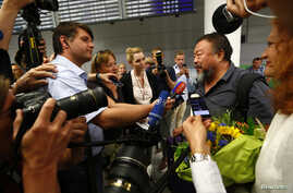 Dissident Chinese artist Ai Weiwei is surrounded by media as he arrives at the airport in Munich, Germany, July 30, 2015.