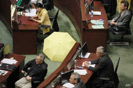 Pro-democracy lawmaker Claudia Mo displays a yellow umbrella before an election for reform proposals in Hong Kong, Thursday, June 18, 2015.