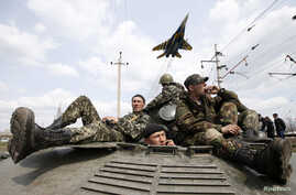 A fighter jet flies above as Ukrainian soldiers sit on an armoured personnel carrier in Kramatorsk, in eastern Ukraine, April 16, 2014.